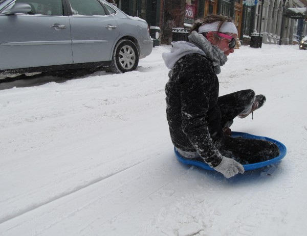 Rebecca Merritt, 21, gets spun around backward as she slides down the middle of Portland's snow-covered Exchange Street on a saucer sled Friday afternoon, Feb. 8, 2012. Cars were sparse on city streets just before 2 p.m. as a 24-plus-hour nor'easter picked up momentum.