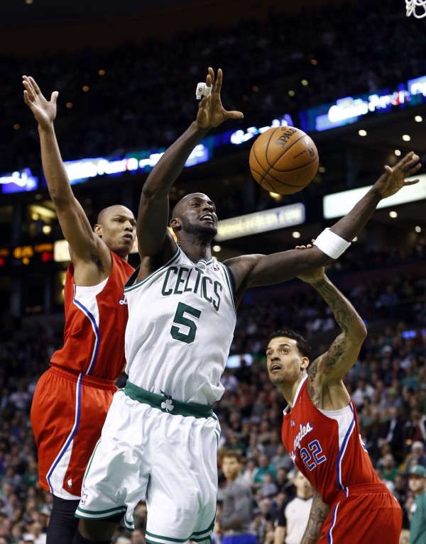 Boston Celtics power forward Kevin Garnett (5) shoots the ball against Los Angeles Clippers small forward Caron Butler (left) and small forward Matt Barnes (22) during the second half at TD Garden.