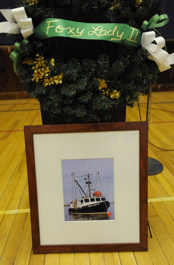 A wreath along with a framed photo of the fishing vessel Foxy Lady II adorn the podium at the Stonington Island Community Center on Sunday during a memorial service for two lost fisherman.