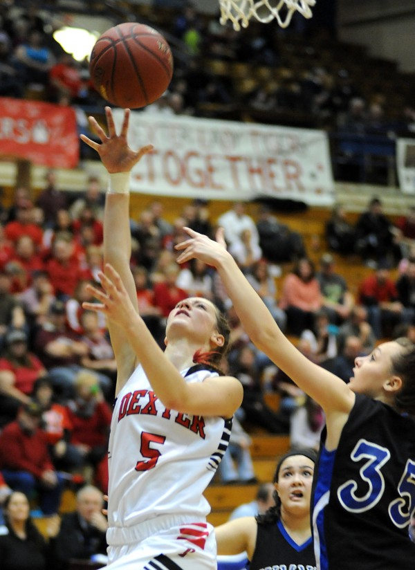 Dexter's Jordyn Bell (left) goes up for a shot as Sumner's Jordan Merchant tries to block in first-half action of the Class C girls quarterfinal game Tuesday morning, Feb. 19, 2013, at the Bangor Auditorium. Dexter won the game 38-36.