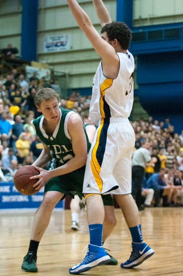 Mount Desert Island's Colin Moores (left) looks for an open teammate against Medomak Valley's Ryan Ripley (right) during the Eastern Maine Class B title game at the Bangor Auditorium on Saturday, Feb. 23, 2013.