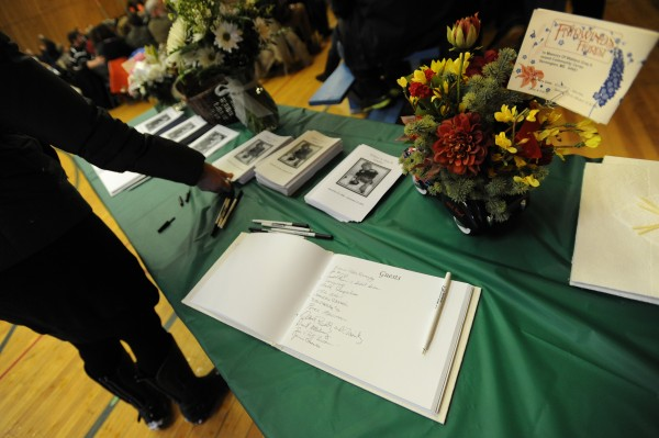 A guestbook along with programs bearing the images of Wayne Kendall Young and Wallace A. Gray II greet guests at the Stonington Island Community Center on Sunday during a memorial service for the two lost fisherman.