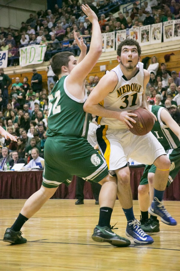 Mount Desert Island's Andrew Davis(left) tries to defend Medomak Valley's Ryan Ripley (right) as he drives to the basket during the Class B state championship game at the Bangor Auditorium on Saturday, Feb. 23, 2013.