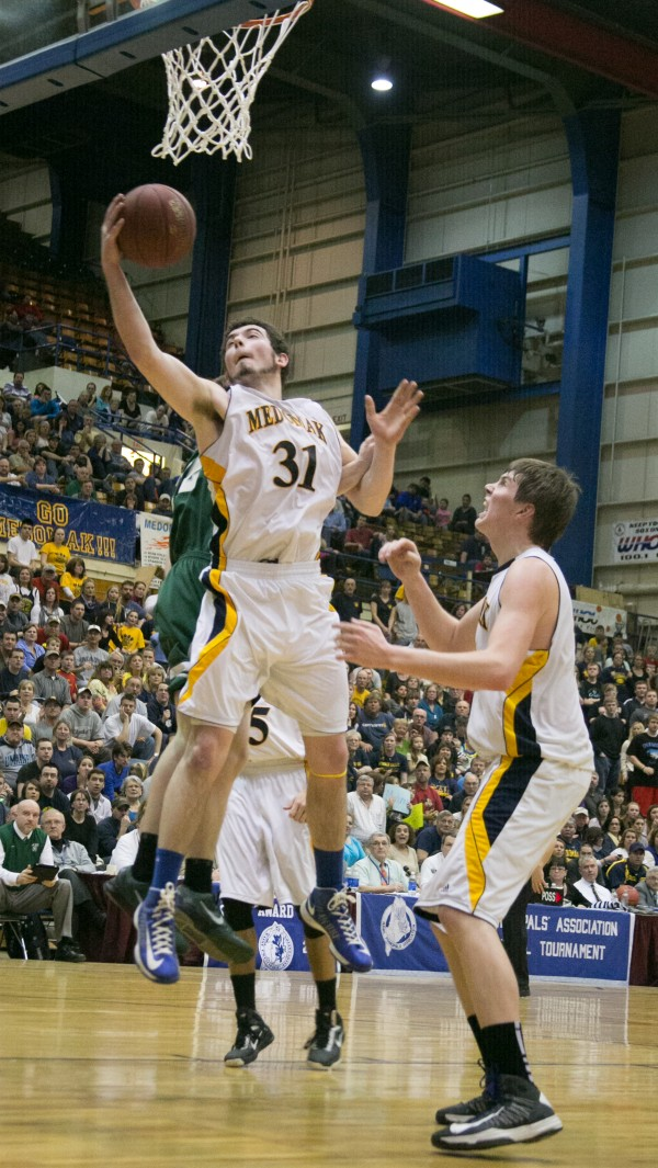 Medomak Valley's Ryan Ripley (left) shoots a layup while teammate John Murray (right) looks on during the Eastern Maine Class B title game at the Bangor Auditorium on Saturday, Feb. 23, 2013.