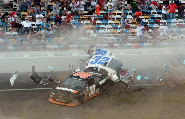 NASCAR driver Kyle Larson's car (32) disintegrates with debris flying into the stands after being involved in a wreck with Brad Keselowski (22) and Brian Scott (2) coming down the front stretch on the final lap of the DRIVE4COPD 300 Nationwide Series race at Daytona International Speedway in Daytona Beach, Fla., Saturday, Feb. 23, 2013. Ten cars were involved in the wreck, and at least 12 spectators were injured.