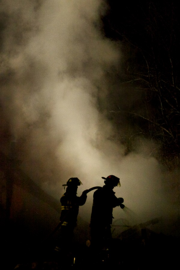 A pair of firefighters look for hot spots in the smoking rubble of a house extension on the Middle Road in Woolwich Tuesday night.