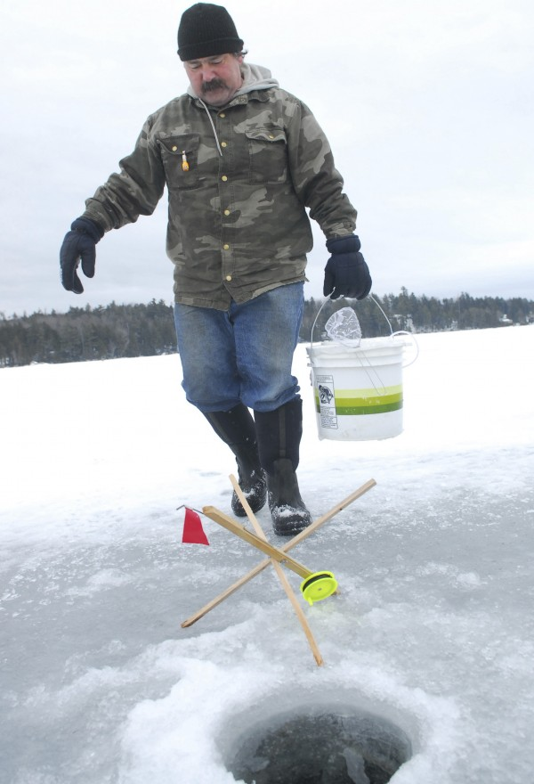 Perry Kep of Ellsworth prepares to bait one of his ice fishing traps at Beech Hill Pond in Otis on Saturday, Feb. 16, 2013, during the Maineiacs Charities Ice Fishing Derby.
