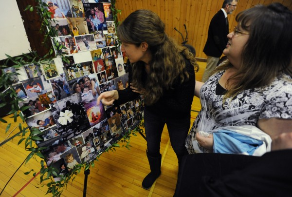 Rya Trundy (left) and Melissa Proper, both family friends of Wayne Kendall Young and Wallace A. Gray II, look at photos of the lost, presumably deceased men, after the memorial service for Wallace A. Gray II, also known as &quotChubby,&quot and Wayne Kendall Young at the Stonington Island Community Center on Sunday.