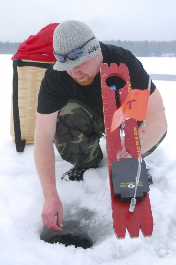 Marcus Files of Brewer sets an ice fishing trap at Beech Hill Pond in Otis on Saturday, Feb. 16, 2013, during the early morning hours of the Maineiac Charities Ice Fishing Derby.