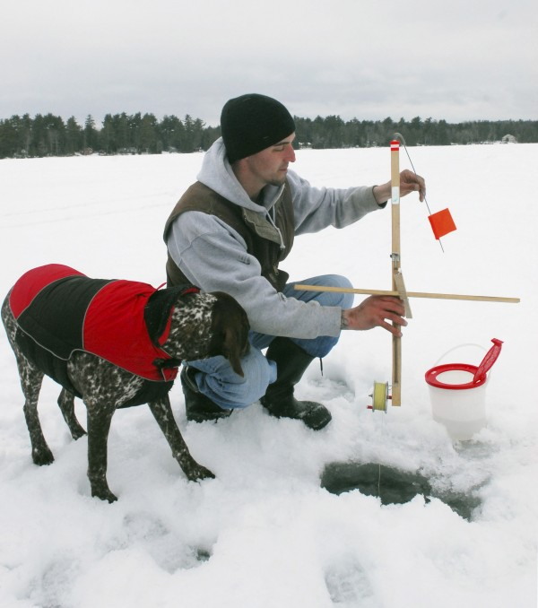 Josh Wright of Otis is eyed by a friend's German shorthair while he sets a ice fishing trap on Beech Hill Pond in Otis on Saturday, Feb. 16, 2013, during the Maineiac Charities Ice Fishing Derby.