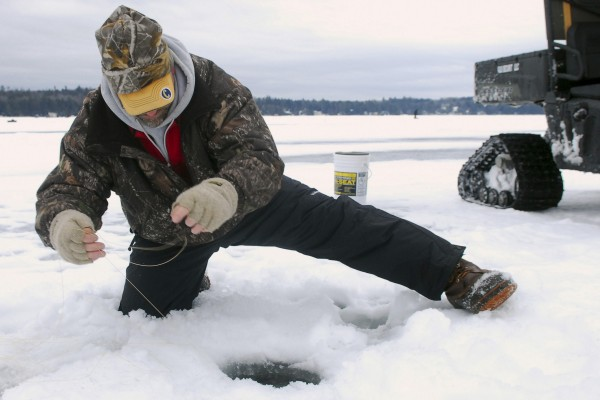 Blair Taylor of Orland pulls in a fish at Beech Hill Pond in Otis on Saturday, Feb. 16, 2013, during the Maineiac Charities Ice Fishing Derby.