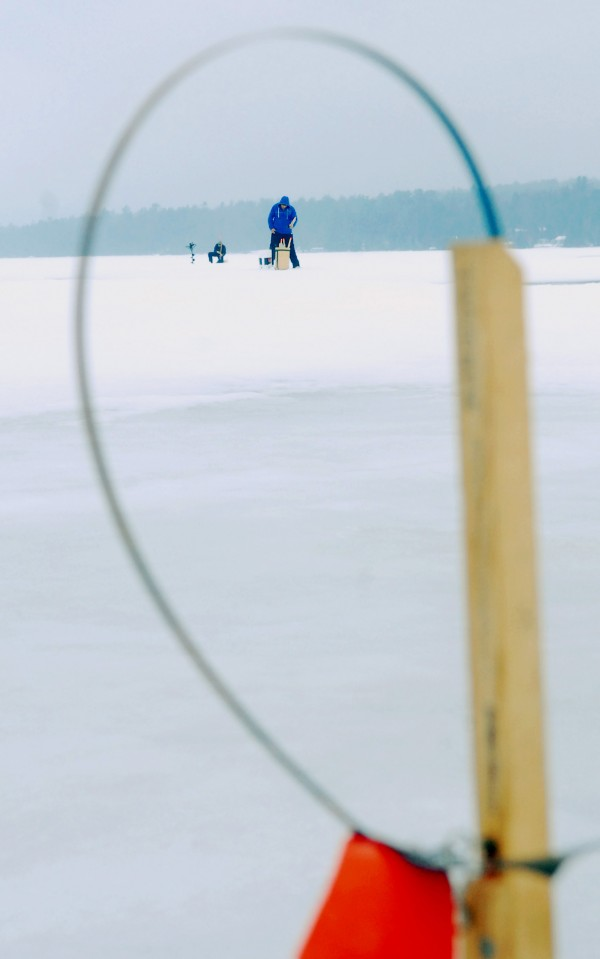 On Beech Hill Pond in Otis Saturday, fishermen are seen setting traps in hopes of catching hefty fish during the Maineiac Charities Ice Fishing Derby.