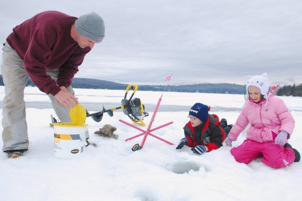 Bart Currie of Charleston is watched by his kids Aidan (left) and Taebria Currie as he sets an ice fishing trap on Beech Hill Pond in Otis Saturday during the Maineiac Charities Ice Fishing Derby. The derby included all legal bodies of water in Hancock County.