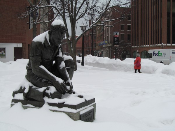 A fresh layer of snow settles on The Maine Lobsterman statue at corner of Temple and Middle streets in Portland as a woman braves the latest precipitation in the background on Monday, Feb. 11, 2013. Contrary to earlier forecasts, the snow turned to rain Monday afternoon, but nonetheless added complication to the ongoing efforts to clean up after a record-setting blizzard less than 48 hours earlier.