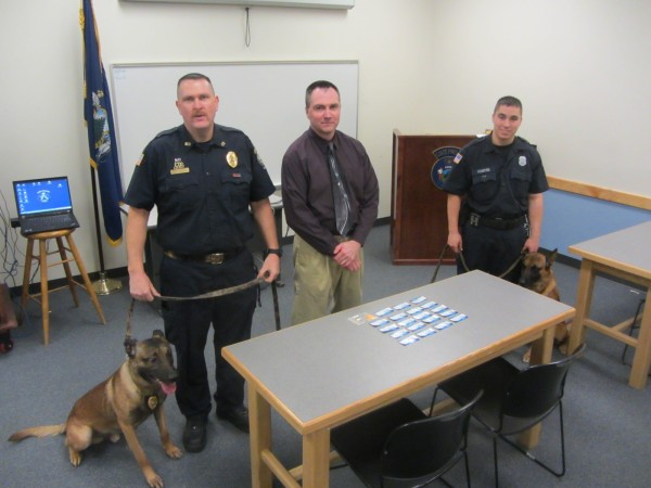 Maine Department of Corrections criminal investigator David Wilson (center) displays suboxone that was seized before it made its way to the Maine State Prison. Also pictured are Corrections Officer Joe Salisbury (from left) with Tyson and Corrections Officer Kyle Sylvester with Gunner.