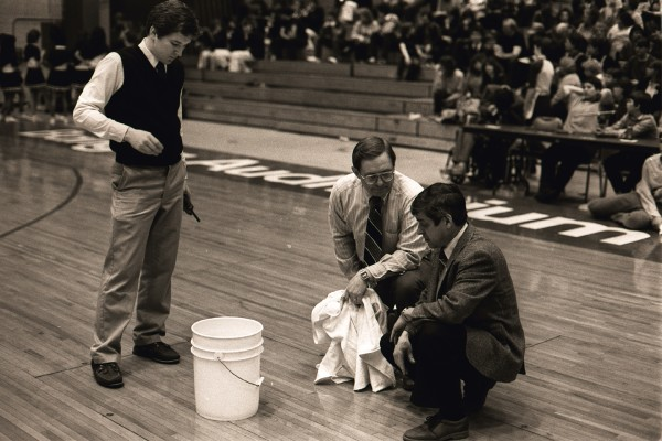 "Fred Olson (left) of the Bangor  Auditorium staff, and Eastern Maine tourney officials Alton ""Bump"" Hadley (center) and Woody Dunphy clean up water on the Auditorium floor from its leaky roof during the Eastern Maine Class B final between Dexter and Rockland on Feb. 21, 1986. Dexter went on to beat Rockland 63-61 in five overtimes."