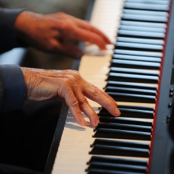 The 95-year-old fingers of Harry Weiss tickle the ivories of a an electronic keyboard at Boyd Place in Bangor on Thursday. Weiss, a former silent movie musician, now plays piano for the pure love of it.