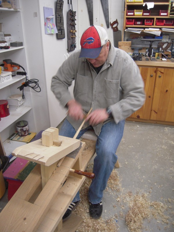 Terry Kelly sits on the shave horse he made and demonstrates how he hews spindles for Windsor chairs he designs and constructs in his workshop in Mapleton.