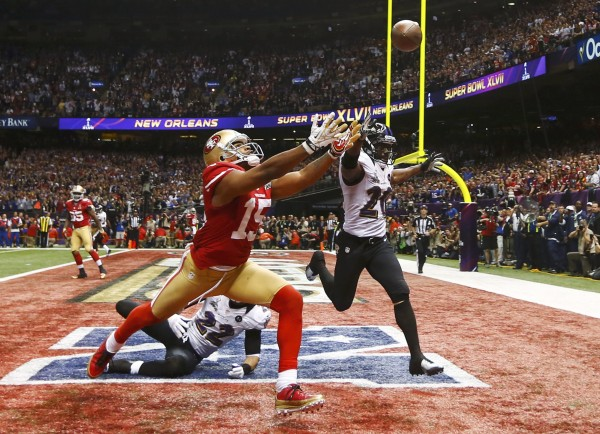 San Francisco 49ers wide receiver Michael Crabtree (15) can't reach a pass while being covered by Baltimore Ravens cornerback Jimmy Smith (22) and Ed Reed during the fourth quarter in the NFL Super Bowl XLVII football game,