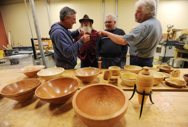 Mike Kagan (left) inspects a flower made from a wood burl by Carl Winter (right) as Stu White (second from left) and Larry Littlefield (second from right) look on during  the January monthly meeting of the Eastern Maine Woodturners at Eastern Maine Community College on Thursday, Jan. 31, 2013.