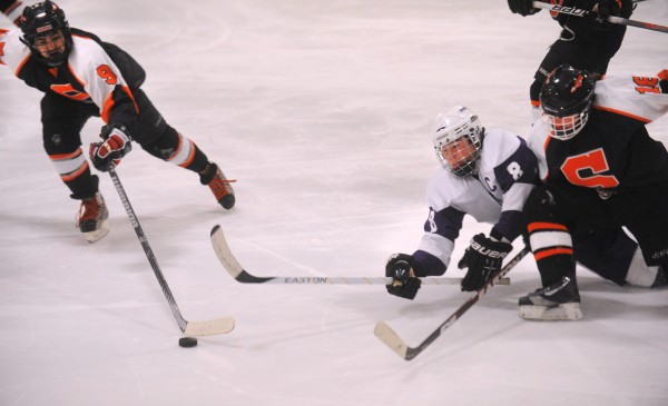 Skowhegan's Anthony James Paul (left) and Ann-Marie Provencal (right) battle for the puck with Hampden's Cooper Antone during a game in Brewer on Jan. 9, 2013.