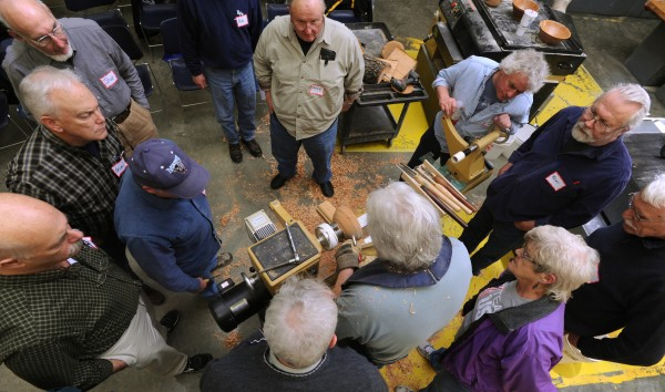 A crowd gathers around Carl Winter as he adds decorative markings on a wooden bowl during a demonstration at Eastern Maine Community College on Thursday, Jan. 31, 2013 during the monthly meeting of Eastern Maine Woodturners.