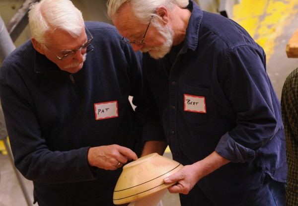 Pat Roche (from left) and Bert Holland, both of Stockton Springs, inspect a wooden bowl that was turned by Carl Winter during a demonstration at Eastern Maine Community College on Thursday, Jan. 31, 2013 during the monthly meeting of Eastern Maine Woodturners.