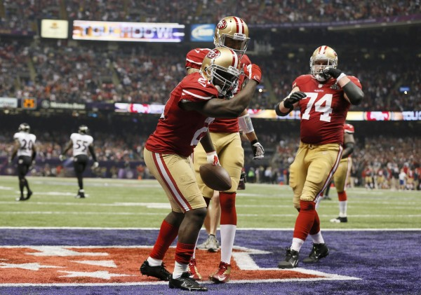 San Francisco 49ers running back Frank Gore (21) celebrates his third quarter touchdown against the Baltimore Ravens with quarterback Colin Kaepernick (7) and teammate Joe Staley (74) in the NFL Super Bowl XLVII football game.