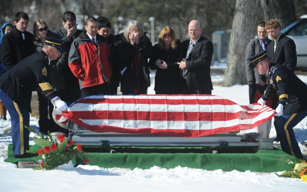 First Sgt. Harold Maker (left) and Sgt. Michael Quint fold the American flag for the family of a deceased veteran at Mount Pleasant Cemetery on Monday. Both are members of the  Maine Army Guard's Maine Military Funeral Honors Program. Monday's honoree was the 9000th veteran to be honored by the program since its inception in 2003.