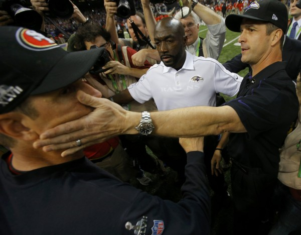 San Francisco 49ers head coach Jim Harbaugh (L) gets a pat on the cheek as he congratulates his brother, Baltimore Ravens head coach John Harbaugh, after the Ravens won in the NFL Super Bowl XLVII football game,