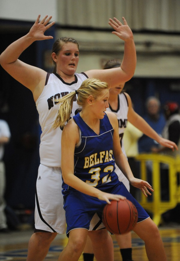 Belfast's Ashley Litlefield is dwarfed by  Nokomis's Traci Carson  as she dribbles toward the hoop during second half action at the Bangor Auditorium on Friday, Feb. 15, 2013.