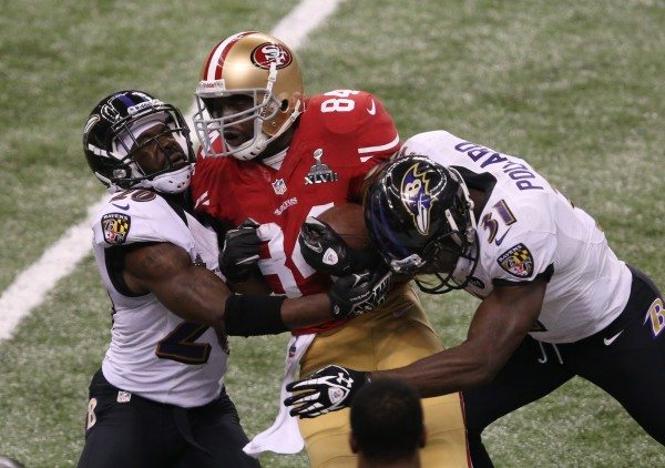 San Francisco 49ers wide receiver Randy Moss (84) is tackled by Baltimore Ravens strong safety Bernard Pollard (31) and free safety Ed Reed (20) in Super Bowl XLVII at the Mercedes-Benz Superdome.