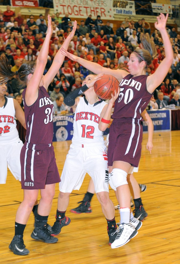 Orono's Katie Smith (left) and Jillian Woodward try to block a shot by Dexter Alison Pease (center) during the first half of the game Friday afternoon.