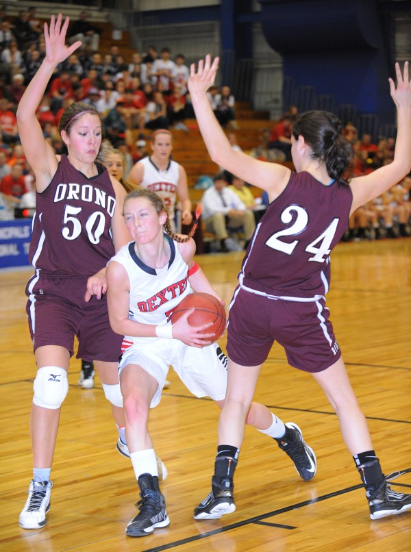 Dexter's Jordyn Bell (center) drives for the basket between Orono's Jillian Woodward (left) and Katie Sypher by during the first half of the game Friday afternoon.