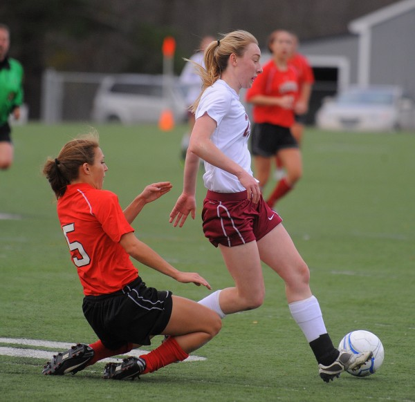 Bangor High School's Grace MacLean pushes the ball ahead of Scarborough's Katie Wahrer during the state final last November in Hampden. MacLean will be continuing her soccer career at the University of Maine this fall.