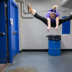 A cheerleader demonstrates how high she can jump in the stairwell of Bangor Auditorium during the Maine state championships.