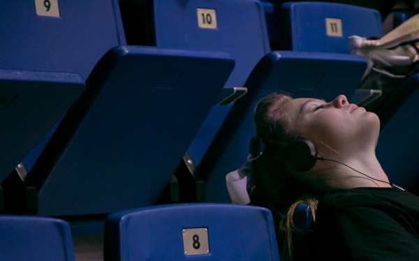 A cheerleader relaxes in the stands behind the competition mat at the Kennebec Valley Conference tournament. Teams often wait hours for their turn to perform.