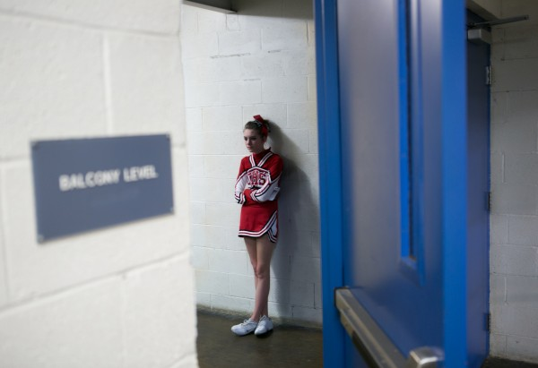 A cheerleader waits in the hallway of Bangor Auditorium before her team performs.