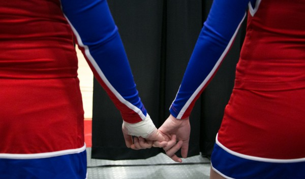 Two cheerleaders hold hands before taking the tumbling mat to perform at the Kennebec Valley Athletic Conference cheerleading competition Jan, 21, 2013.