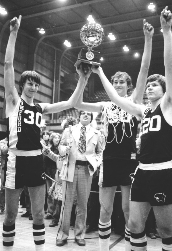 Rumford tri-captains Andy Shorey (from left), Tim Ziko and Matt Kaubris hold aloft the gold ball after beating the Stearns Minutemen for their second straight state title at the Bangor Auditorium on March 19, 1977.