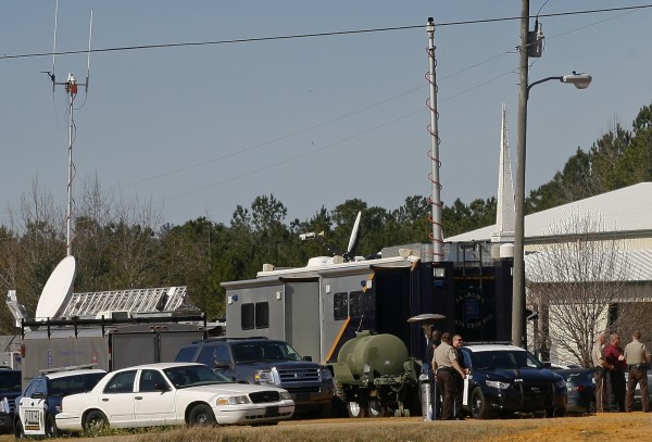 Law enforcement officials man a command center Sunday set up at Destiny Church near the scene of a shooting and hostage-taking outside Midland City, Ala. A gunman boarded an Alabama school bus ferrying children home from school on Tuesday and fatally shot the driver before fleeing with a young child; they have been holed up in an underground bunker ever since, Alabama media reported.