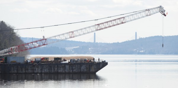 A barge carrying a crane to be used in the dismantling of the old Waldo Hancock Bridge in Prospect rounds a corner in the Penobscot River near Winterport on Tuesday.