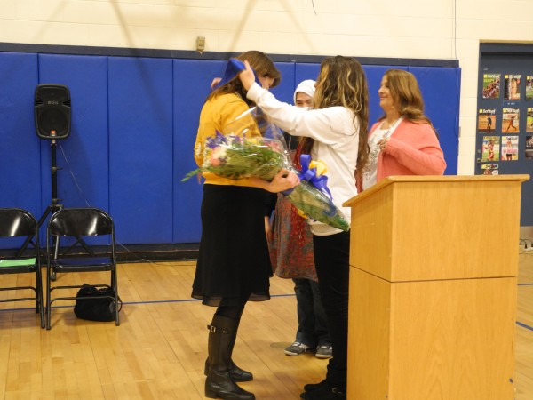 Kimberly Buckheit, the principal of Troy Howard Middle School in Belfast, receives a sash and a bouquet of flowers from Emily Harriman, 13, the student council president during a ceremony to honor Buckheit's selection as Maine's Middle Level Principal of the Year by the Maine Principals' Association.