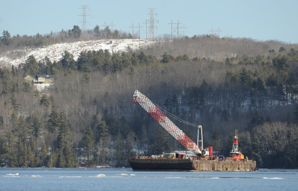 A barge carrying a crane to be used in the dismantling of the old Waldo Hancock Bridge in Prospect is pushed down the Penobscot River near Winterport on Tuesday.
