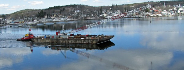 A 250-by-75-foot barge cruises past Bucksport en route to the Waldo Hancock Bridge, where the 262-foot crawler crane will lower pieces of the bridge to shore in a massive project to demolish the bridge, expected to end in July.