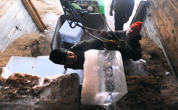 Todd Stevens of New Portland (left) and Chas Gill of Bowdinham wrestle a block of ice on the top of the stack in the ice house at Cobb's Pierce Pond Camps on Saturday, Feb. 2, 2013. The ice is usually cut to a certain size but the weight of the blocks can vary depending on the thickness of the pond ice. The blocks this year weighed in around 140 pounds.