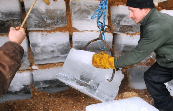 Todd Stevens of New Portland pushes a block of ice into place as they are stacked in the ice house at Cobb's Pierce Pond Camps on Saturday, Feb. 2, 2013. The ice is stacked in sawdust and snow and is used at the camps throughout the season.