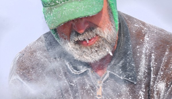 David Peppard of Eddington is engulfed in the fine chips of ice thrown by the ice saw while working at Cobb's Pierce Pond Camps in Pierce Pond Township. Peppard is one of the several guides who works at the camps during the fishing season and is a regular participant in the annual ice harvest.