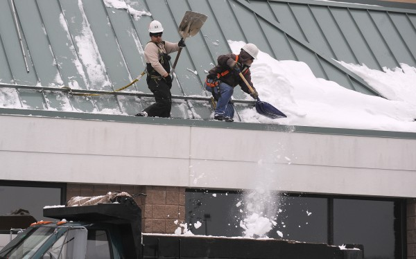 Jason Freeman (left) and Norm L'Heureux with the Augusta-based G&E Roofing clear snow from the roof of the Hannaford store at the Airport Mall Monday.  They said the heavy snow fall keeps them busy.