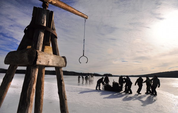 The ice saw is dragged by people as they make the initial cuts on the ice at Cobb's Pierce Pond Camps during the 2013 ice harvest.  The harvest was restarted by Gary Cobb in the mid-1970s as a novelty and and to provide some additional refrigeration for food and drinks at the camp. The equipment on the left — refereed to as a galamander by the crew — is used to lift the ice blocks from the water.